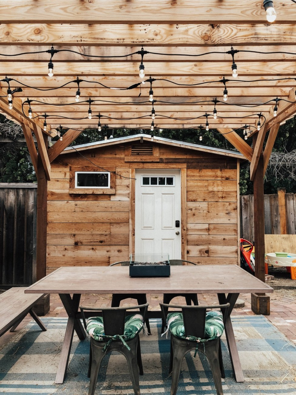 Elevate your outdoor dining experience by hanging cafe lights on your pergola or string them across to a tree. #outdoordining #cafelights #woodpergola #homeupdates