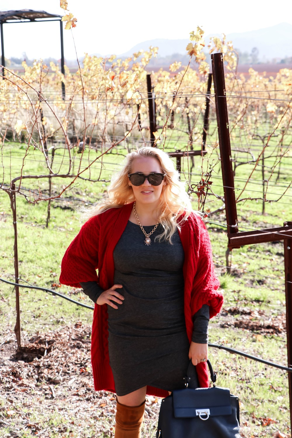 Wearing a red cable knit sweater and long sleeve bodycon dress for a festive winter look - Have Need Want #winterstyle #outfitinspiration #cableknitcardigan #bodycondress