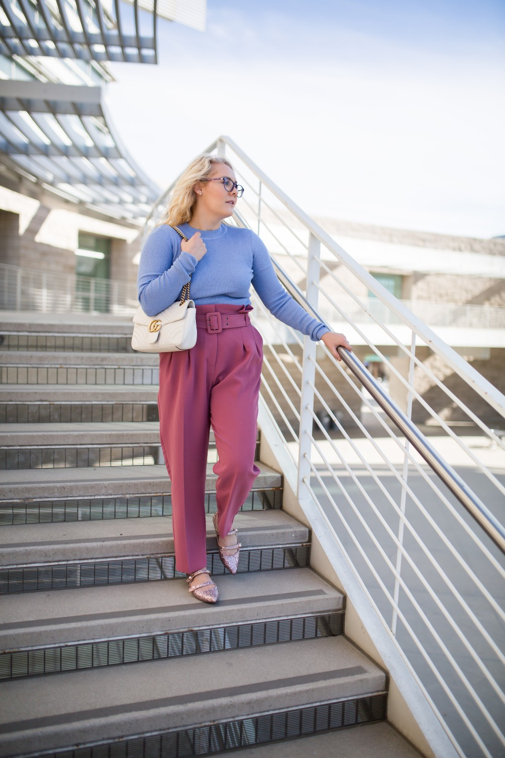 Girl wearing glasses periwinkle blue sweater and blush pink pants