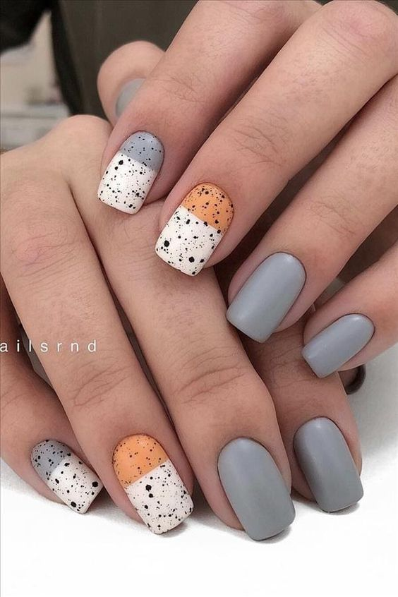 Neutral manicure with grey, tan, white, and splattered black design.