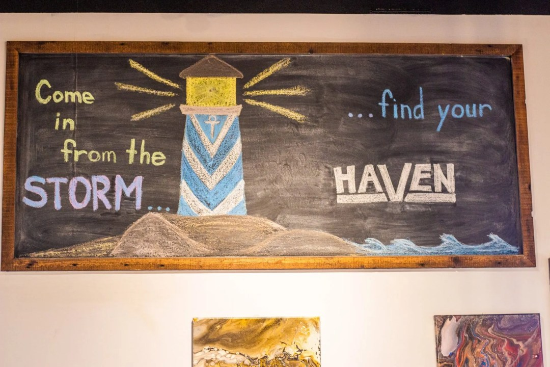 """Photo of chalkboard with drawing of lighthouse and writing """"Come in from the storm...find your Haven."""""""