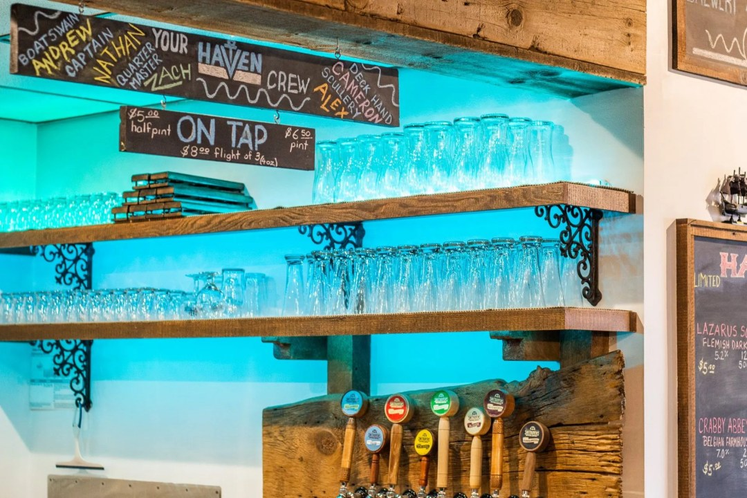 Picture of behind the bar with glasses, taps, and sign listing the team members.