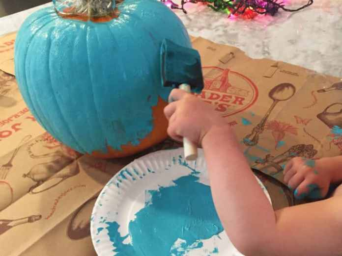 A child paints a pumpkin teal