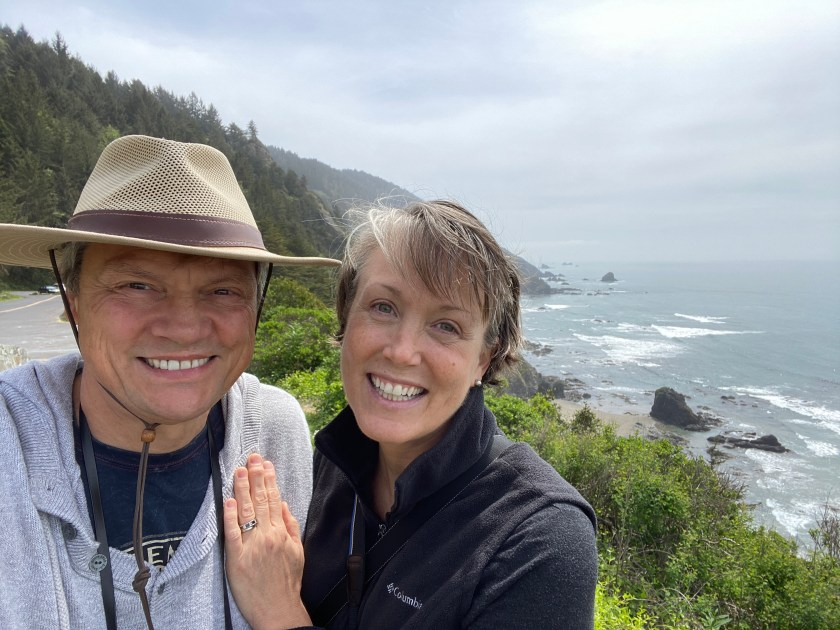 A couple standing near the wooded shore at the ocean near Crescent City, CA