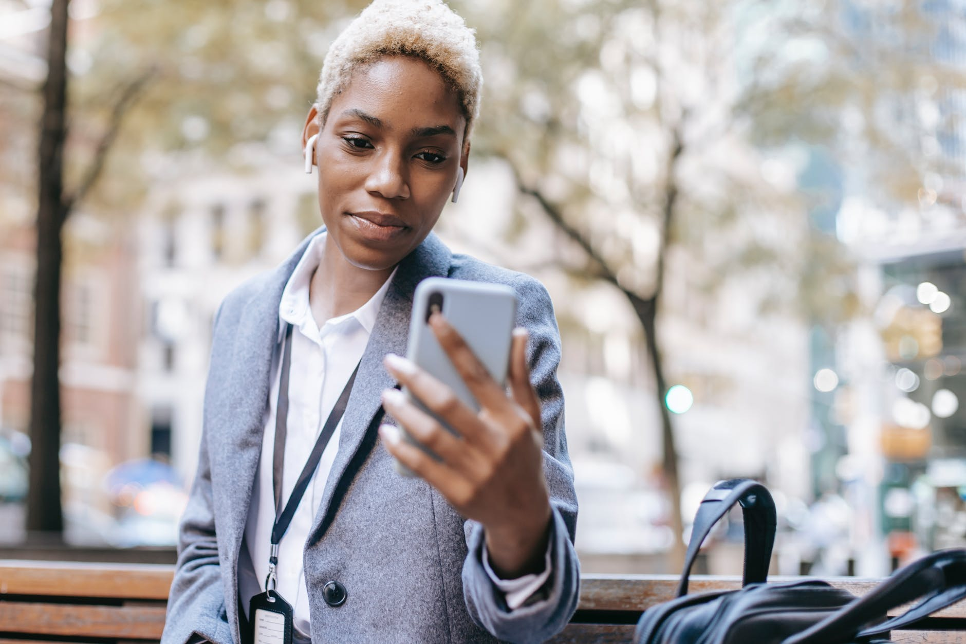 positive black woman reading text message on smartphone