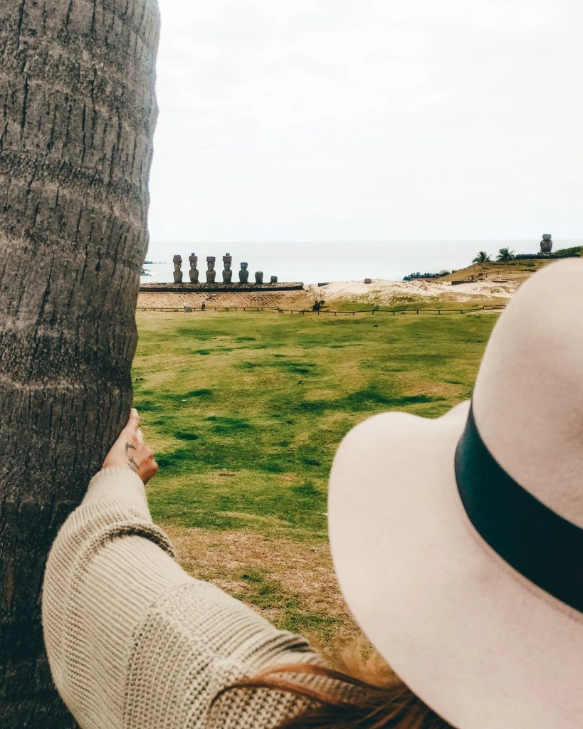 A woman looking at the moai statues of Anakena Beach on Easter Island.