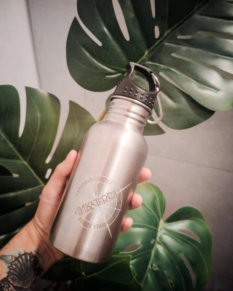 A hand holding a metal reusable water bottle in front of green plants