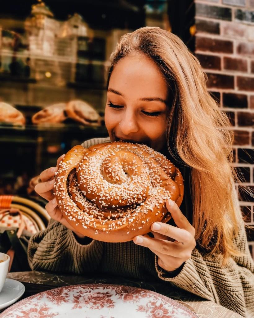 A woman eating a large cinnamon bun in Gothenburg, Sweden.