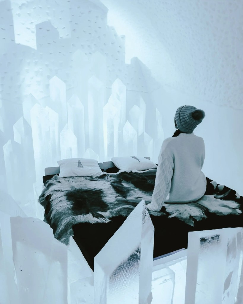 Woman sitting inside a cold art room at Sweden's ice hotel.