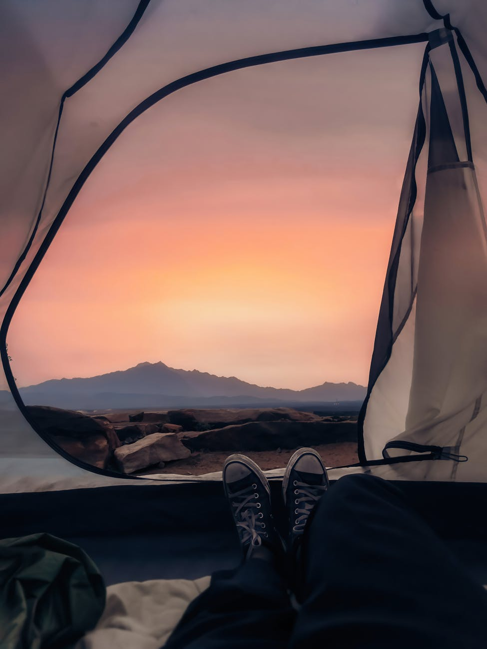 traveler lying in tent and enjoying bright sunset light