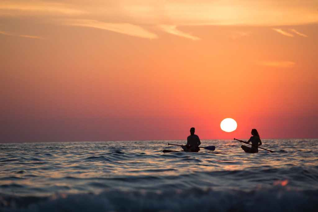 man and woman boat rowing in sea during golden hour