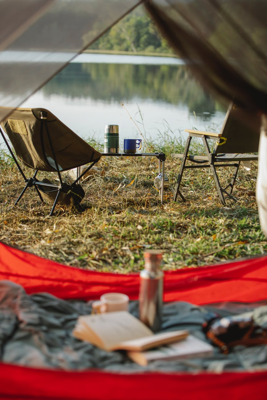 camping chairs and tent near calm lake