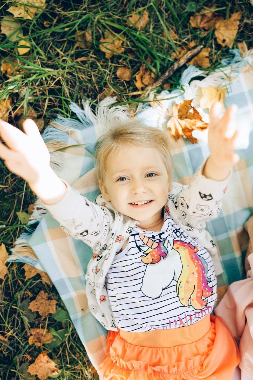 girl in white and blue polka dot long sleeve shirt lying on green grass field