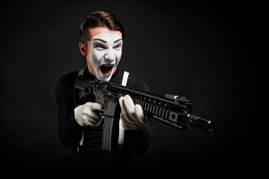 Crazy smiling and screaming mime with rifle in hand on black background