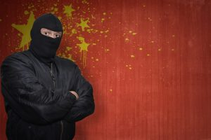 dangerous man in a mask standing near a wall with painted national flag of china