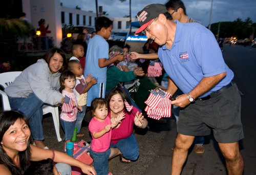 Russell Hayashi of the Exchange Club passes out flags to the crowd during the Lehua Jaycees Island Style Christmas parade in Hilo.