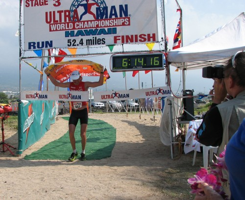 Miro Kergar flies the Slovenian flag as he crosses the finish line Sunday, Nov. 30, 2008 at Old Airport Beach Park in Kailua-Kona. His second place run time was good enough to earn him the Ultraman third place overall.