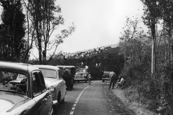 Spectators seeking a closer view of lava climbed up the levees of a thick 'a'ā flow that crossed Highway 11 during the June 1950 eruption of Mauna Loa.  Stories of this and other lava flows in Ka'ū and Kona will be recounted by USGS scientists in upcoming public talks.  Photo: U.S. Army Air Corps.