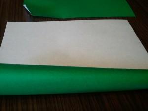 5,茎の部分を作って行きます。緑色の折り紙をくるくると丸めて行き、