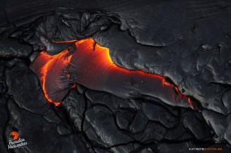 The edge of a flow lifts up as pressure builds within, releasing a new lobe of molten pahoehoe.