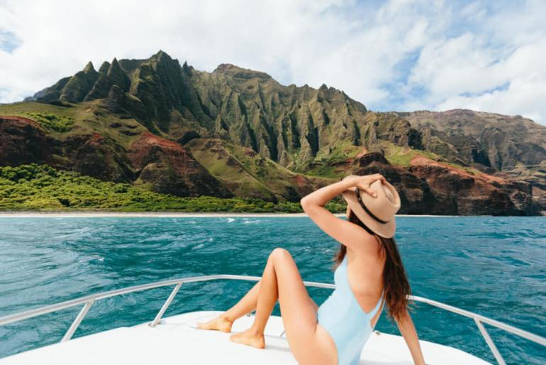 A woman sits on a boat in front of the Na Pali Coast on Kauai