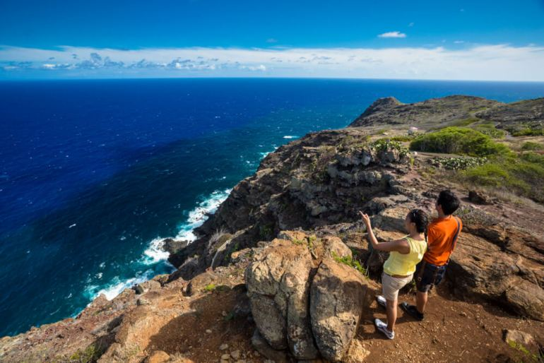 Oahu or Kauai: Which is the Best Hawaiian Island for Kids? Tips featured by top Hawaii travel blog, Hawaii Travel with Kids: Couple look across the Pacific from Makapuu Trail