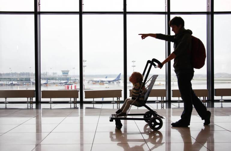 Get my tips for flying to Hawaii with a toddler. Image of a man pushing a stroller while pointing at an airport.