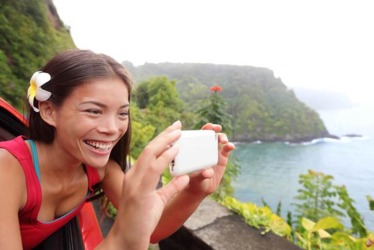 Renting a car in Hawaii is a smart idea. Image of a tourist on Hawaii taking photo with camera phone during car road trip on the famous Road to Hana
