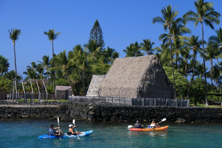 The Best Things to Do in Kona Hawaii featured by top Hawaii blog, Hawaii Travel with Kids: Kayakers cross Kamakahonu Bay near Ahuena Heiau, Historic Kailua Village