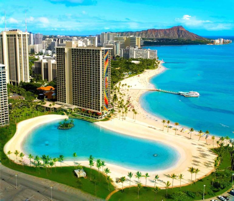 The Hilton Hawaiian Village is one of the Best Resorts in Oahu for Families. Image of Waikiki Beach and the pool area at the Hilton Hawaiian Village Oahu Resort.