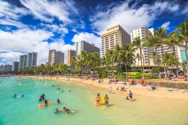 When planning trip to Hawaii, avoid Japan's Golden Week (end of April to early May.) Hawaii gets a ton of Japanese tourists that week and it's an expensive time to visit Hawaii. Image of a crowded Waikiki beach.
