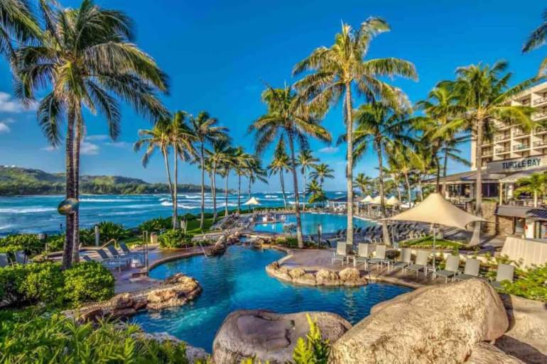 Turtle Bay Resort is a top North Shore Oahu hotel. Image of a tropical pool area by the ocean.