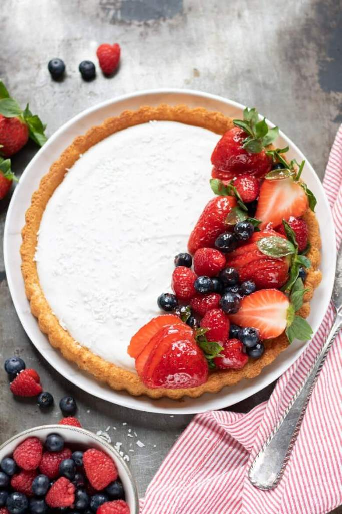 61 Delicious Coconut Dessert Recipes Perfect for Summer featured by top Hawaii blog, Hawaii Travel with Kids: Overhead shot of a Coconut Fruit Flan piled with glazed berries on a sponge flan case. With berries scattered next to it.