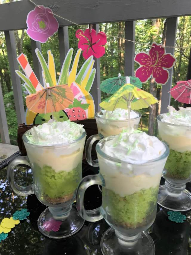 61 Delicious Coconut Dessert Recipes Perfect for Summer featured by top Hawaii blog, Hawaii Travel with Kids: Close up key lime coconut parfaits with luau flowers and decorations