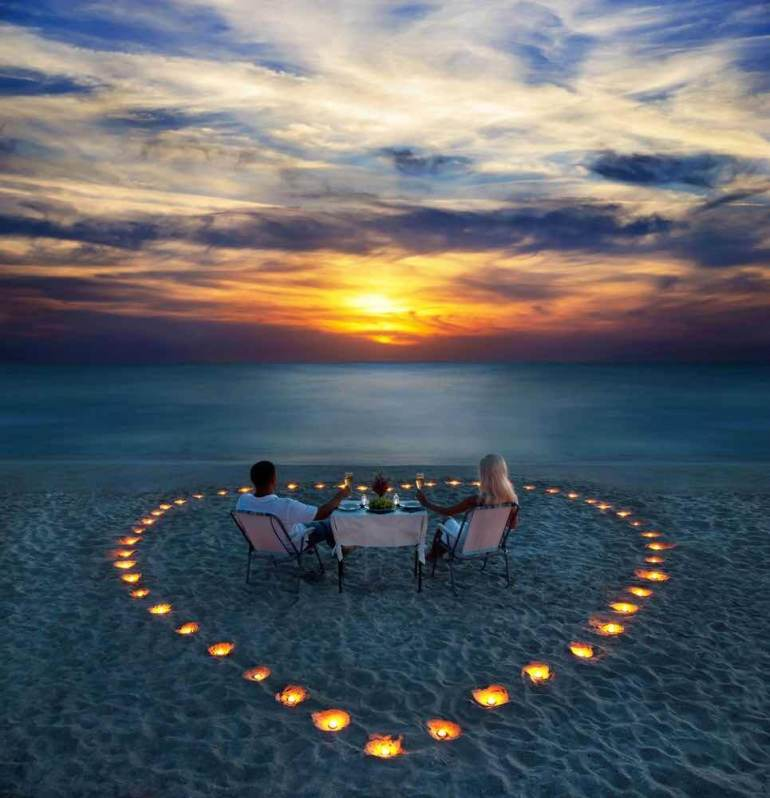 Top 10 Romantic Hawaii Beach Proposal Ideas + Locations featured by top Hawaii blog, Hawaii Travel with Kids: A young couple share a romantic dinner with candles heart on the sea sand beach
