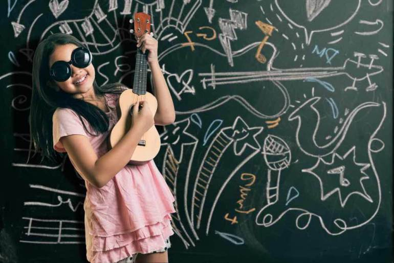 Find out whether you should buy an ukulele for kids in this children's ukulele buying guide. Image of a girl wearing sunglasses and playing the ukulele in front of a chalkboard