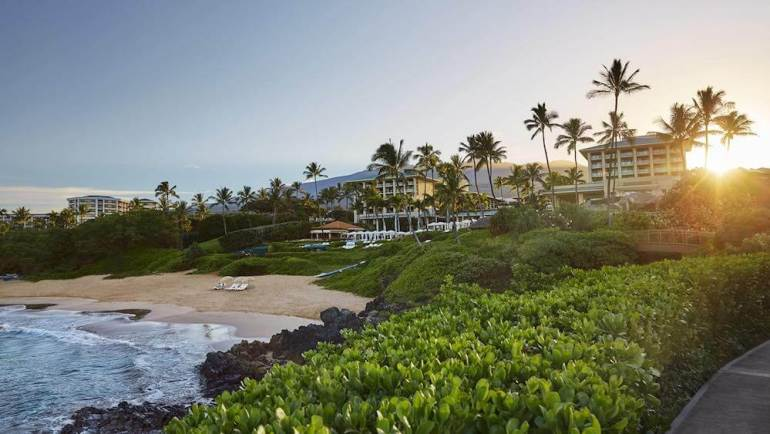Top 5 Best Maui Luxury Hotels featured by top Hawaii blogger, Hawaii Travel with Kids: The Four Seasons Maui is a top Maui Luxury Resort perfect for couples. Image of the exterior of a waterfront hotel in Maui