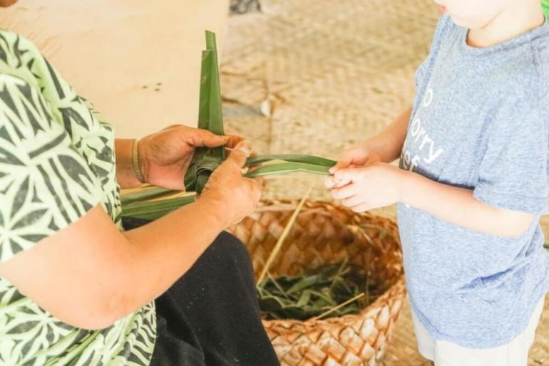 The Polynesian Cultural Center is the best rated luau in Oahu. Image of a boy learning how to weave lauhala at the Polynesian Cultural Center in Laie Oahu.