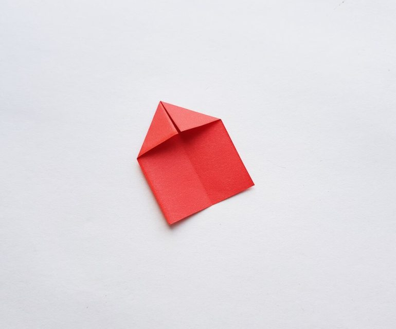 How to Make Origami Poinsettia Flowers, a Hawaiian Christmas craft tutorial featured by top Hawaii blogger, Hawaii Travel with Kids: Image of a piece of red paper folded with a triangle on top