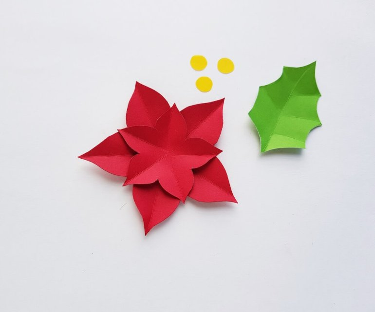 How to Make a Paper Poinsettia Craft, a tutorial featured by top Hawaii blog, Hawaii Travel with Kids: Image of pieces of paper cut out and partially assembled to form a poinsettia