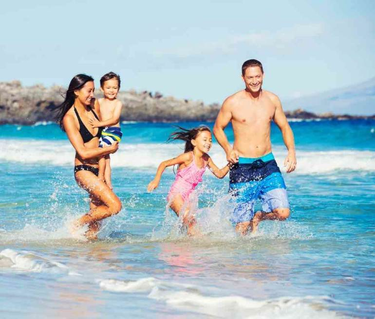 Planning a Hawaii tripi? Don't go for just the weekend. Image of Young Happy Family Playing Having Fun at the Beach Outdoors