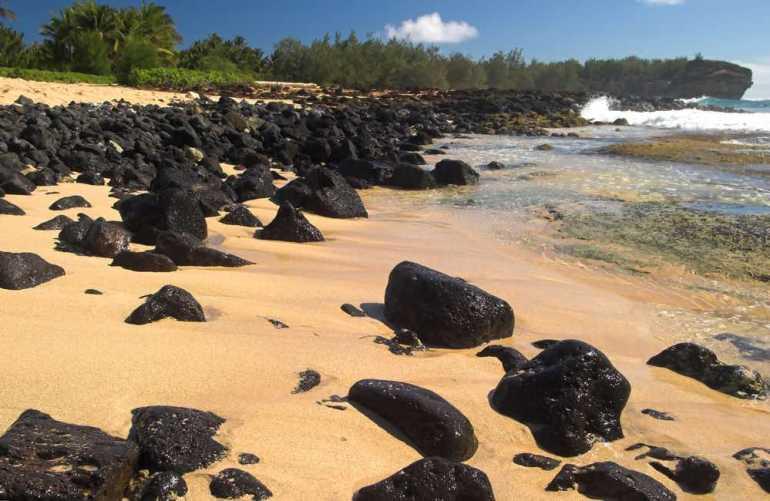 Shipwreck Beach is a top sunset Kauai spot. Image of Shipwreck Beach with black volcanic boulders, Kauai, Hawaii