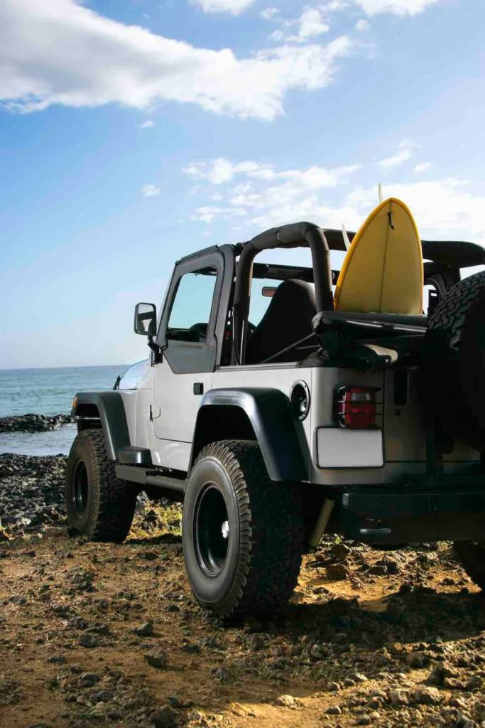 One of my top Maui tips is to rent a car. Image of SUV parked at beach with surfboard in Maui, Hawaii.