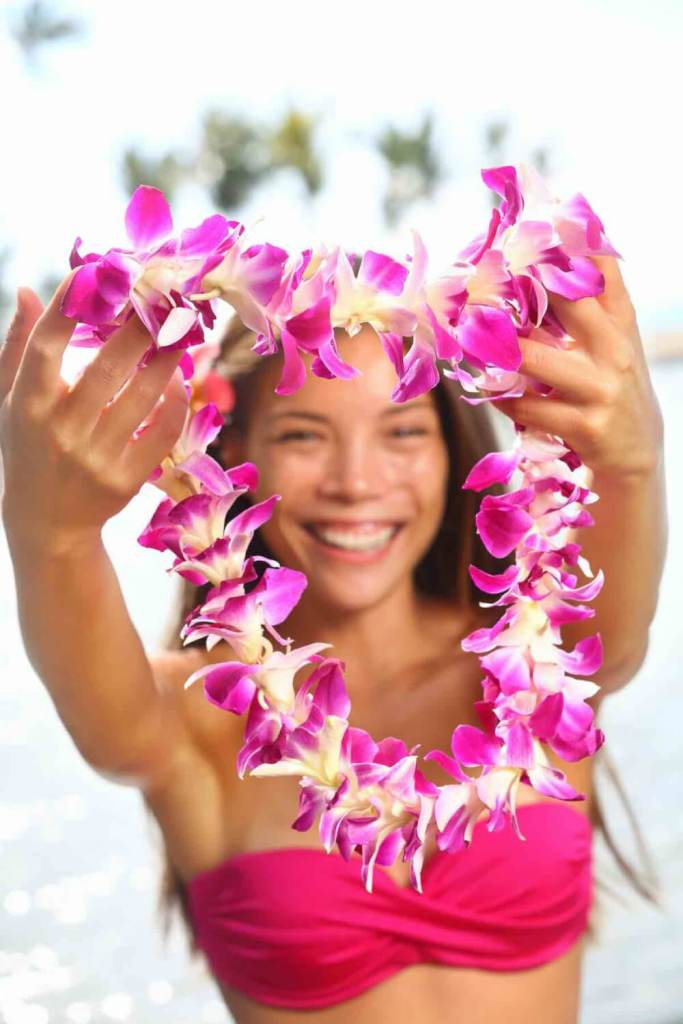 If you're planning a Hawaii trip, don't expect to get a fresh flower lei when you arrive in Hawaii unless you book it ahead of time. Image of Hawaii woman showing flower lei garland of pink orchids. Beautiful smiling mixed race woman in bikini on beach giving a welcoming Lei on the Hawaiian island Big Island.