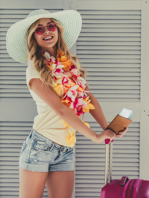 Find out what you might forget on your Hawaii packing list. Image of a woman wearing a large white straw hat, sunglasses, and a lei holding a passport and a pink rolling suitcase, ready for her first trip to Hawaii.
