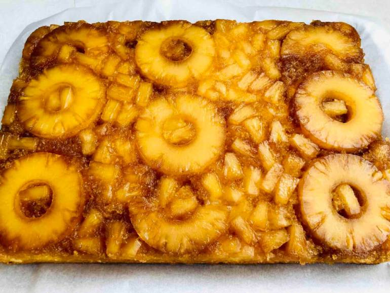 Image of a fully cooked pineapple upside down cake that has been flipped onto a heat-safe surface.