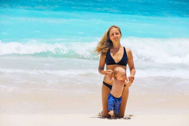 Read this baby-friendly Hawaii guide by top Hawaii blog Hawaii Travel with Kids. Image of On sunny white sand beach happy young mother hold on hands little baby son, have fun before swimming in sea. Active children, travel lifestyle, summer vacation with kids on tropical family resort.