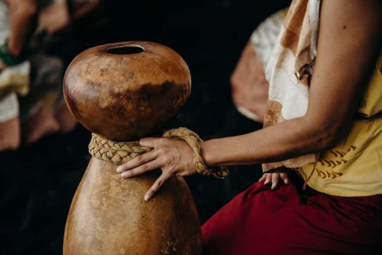 Image of a woman playing traditional Hawaiian music with an ipu heke (double gourd drum.)