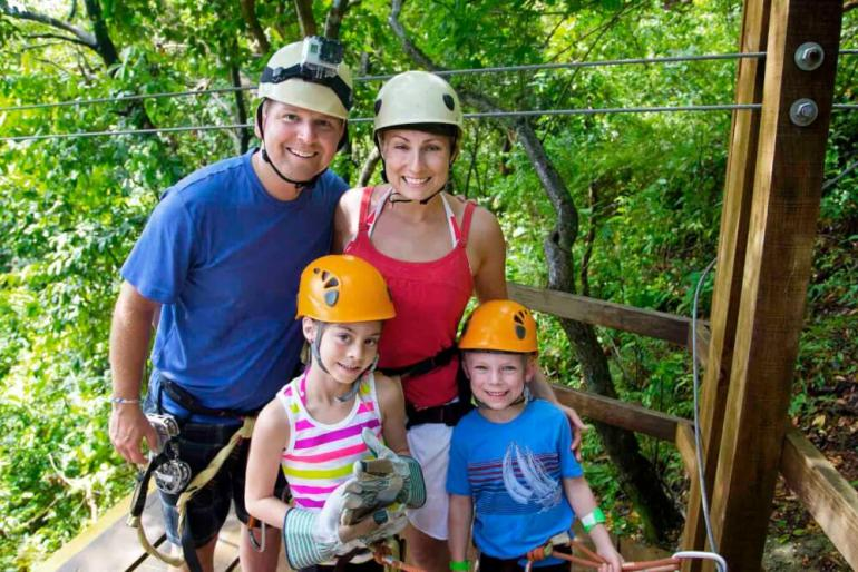 One of the best things to do with kids on Maui is go ziplining! Family with little kids pose for a photo wearing helmets before ziplining on Maui.