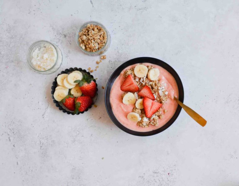 Add your favorite toppings to this mango strawberry smoothie bowl. Image of a tropical smoothie bowl with small bowls of fresh fruit, coconut flakes, and granola.